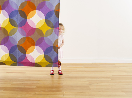 Smiling little girl hiding behind curtain LANG_EVOIMAGES