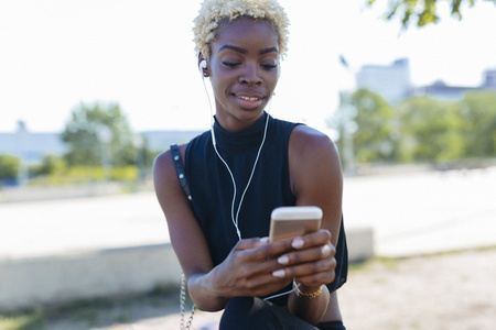 Smiling young woman with cell phone and earbuds