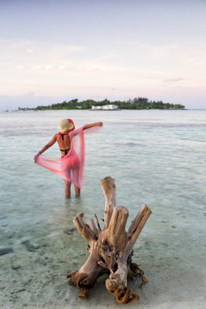 Maldives, Guraidhoo, woman standing in shallow water at sunset LANG_EVOIMAGES