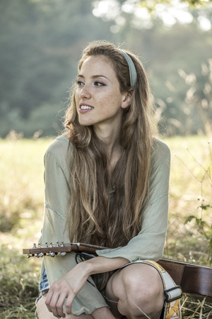 Young woman with guitar on meadow LANG_EVOIMAGES
