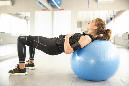 Woman training with electrical muscle stimulation on gym ball
