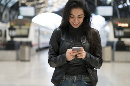 Happy young woman with cell phone at train station