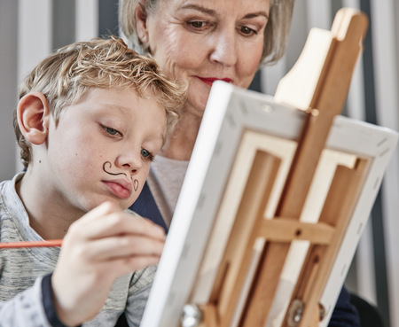 Grandmother and grandson with Dali moustache at easel LANG_EVOIMAGES