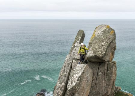 UK, Cornwall, woman on peak of Commando Ridge climbing route