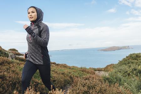 Ireland, Howth, woman running on coastal path
