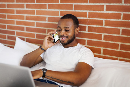 Smiling young man on bed using laptop and cell phone