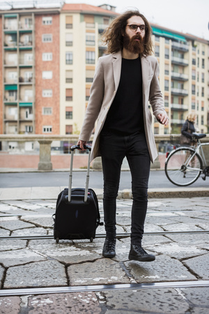 Stylish young man with suitcase crossing tramway LANG_EVOIMAGES