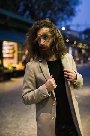 Stylish young man outdoors at night