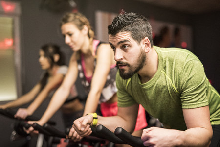 Young people exercising on spinning bikes in gym