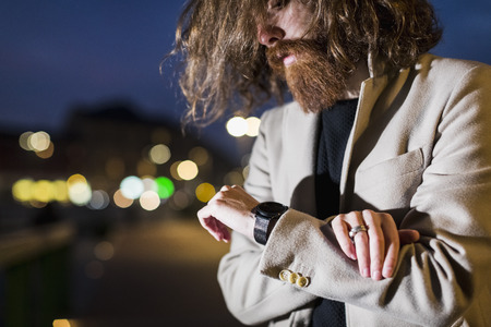Stylish young man outdoors at night checking the time LANG_EVOIMAGES
