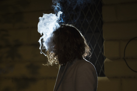 Silhouette of young man surrounded by a cloud of smoke outdoors at night LANG_EVOIMAGES