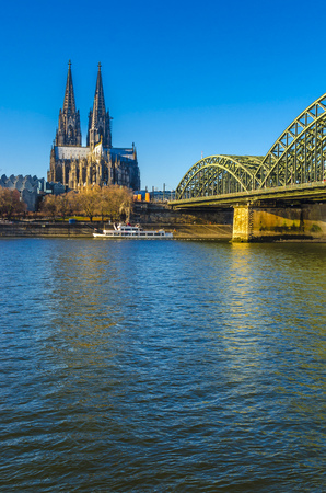 Germany, Cologne, view to Cologne Cathedral with Hohenzollern Bridge and Rhine River in the foreground LANG_EVOIMAGES