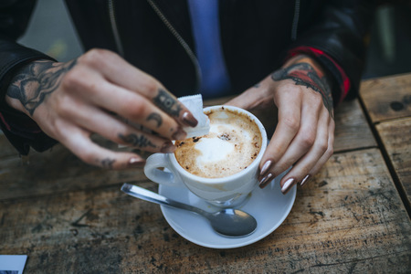 Womans tattooed hands pouring sugar into cup of coffee, close-up LANG_EVOIMAGES