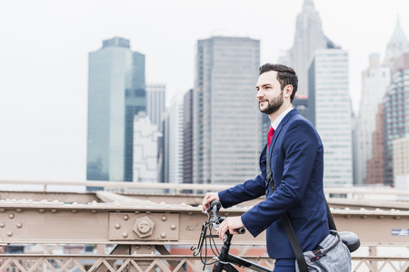 USA, New York City, businessman with bicycle on Brooklyn Bridge