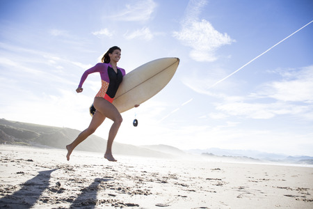 Woman carrying surfboard running on the beach