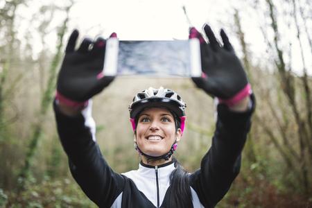 Smiling female mountain biker taking a selfie