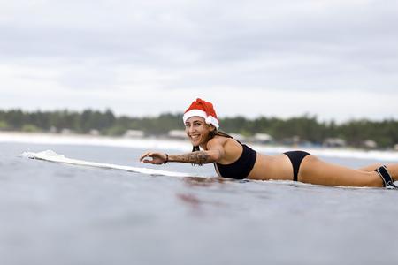 Indonesia, Bali, smiling woman on surfboard wearing Santa hat