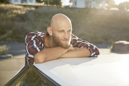 Portrait of bald young man with beard leaning on car roof