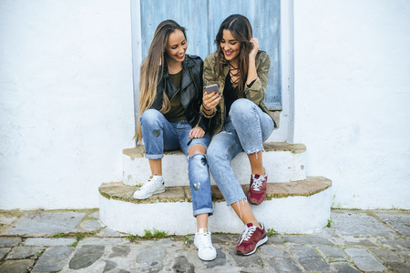 Two young women sitting on stoop looking at cell phone LANG_EVOIMAGES