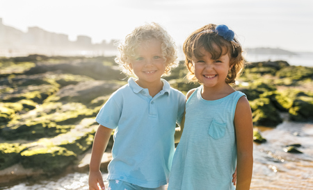 Portrait of happy little boy and girl side by side on the beach LANG_EVOIMAGES