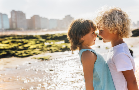 Little boy and girl face to face on the beach LANG_EVOIMAGES