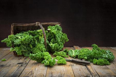 Wickerbasket of kale leaves and pocket knife on wood