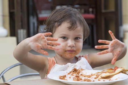 Portrait of little girl eating spaghetti with fingers