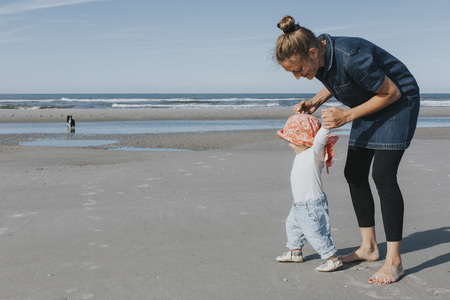 Netherlands, Schiermonnikoog, mother walking with little daughter on the beach
