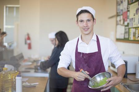 Portrait of teenage boy in cooking uniform in high school class