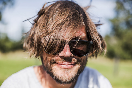 Portrait of a man with unkempt hair wearing sunglasses LANG_EVOIMAGES
