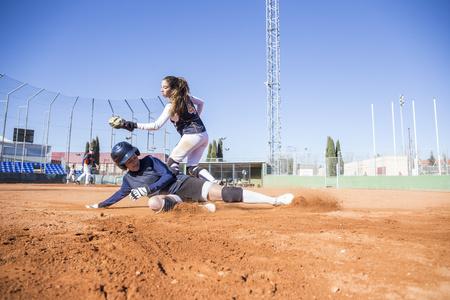 Baseball player sliding to the base during a baseball game