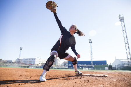 Female baseman catching the ball during a baseball game LANG_EVOIMAGES
