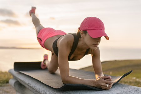 Young woman doing strength training on a bench at the sea