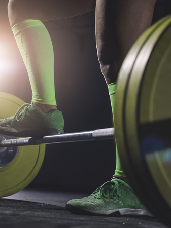 Close-up of woman standing at barbell