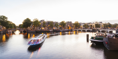 Netherlands, Amsterdam, view to the old town and Magere Brug with Amstel River in the foreground LANG_EVOIMAGES