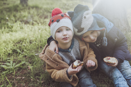 Two boys eating Berliners in forest