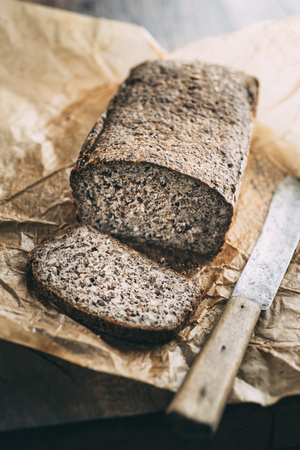 Home-baked wholemeal gluten-ree bread and bread knife on brown paper LANG_EVOIMAGES