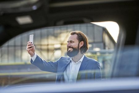 Smiling businessman taking a selfie outside car LANG_EVOIMAGES