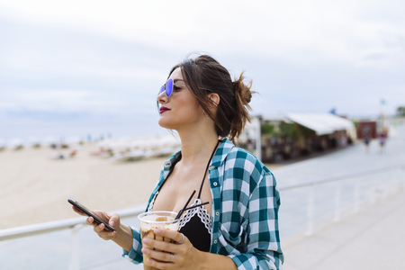 Young woman at the beach with cup of coffee and smart phone