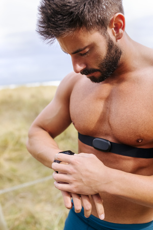 Barechested athlete outdoors looking on smartwatch
