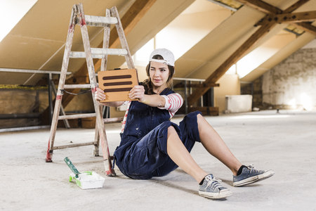 Young woman sittig on construction site, usind digital tablet