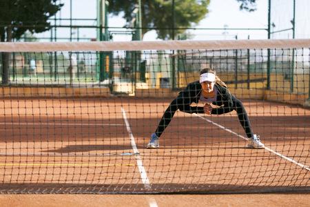 Teenage girl warming up on tennis court