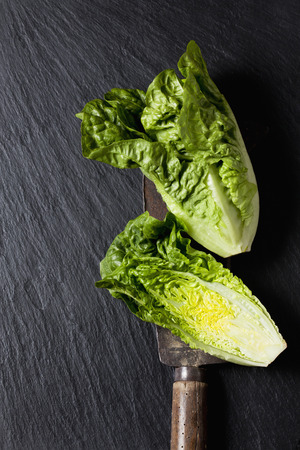 Whole and sliced romaine lettuce and an old knife on slate