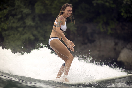 Indonesia, Java, smiling woman surfing