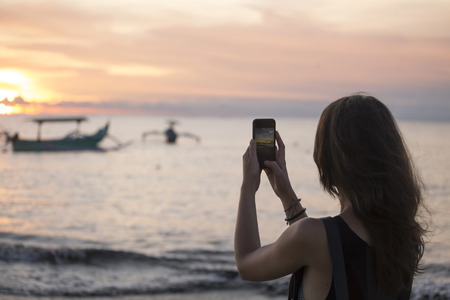 Indonesia, Bali, woman taking a picture of the sunset over the ocean LANG_EVOIMAGES