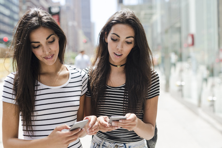 USA, New York City, two twin sisters looking at cell phones in Manhattan