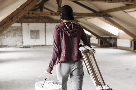 Young woman on construction site carrying ladder and paint bucket