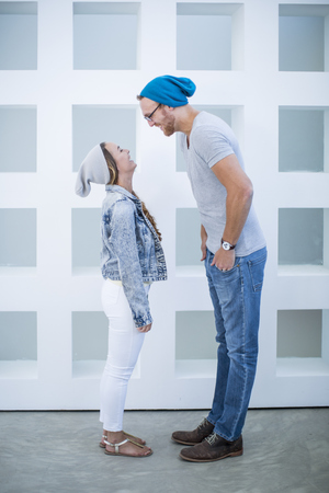 Short woman and tall man laughing at each other LANG_EVOIMAGES