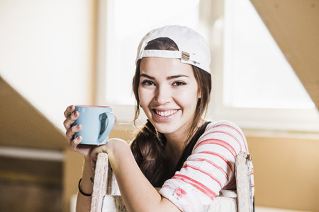 Young woman on construction site holding cup of coffee LANG_EVOIMAGES