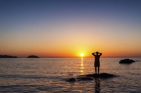 Spain, Menorca, Playa de Cavalleria, man on rock in the sea at sunset LANG_EVOIMAGES